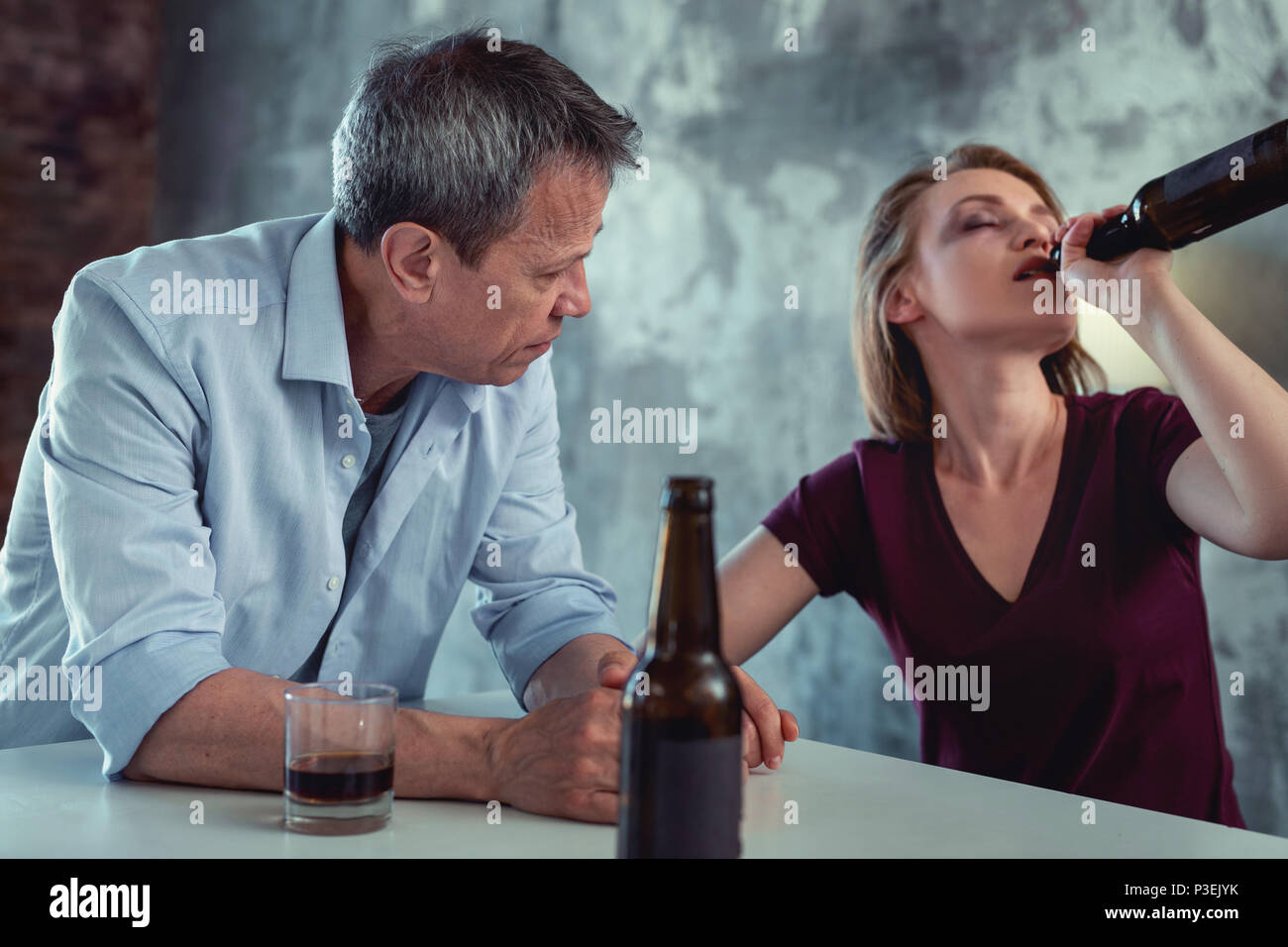 White collar worker feeling concerned looking at drunk wife - Stock Image