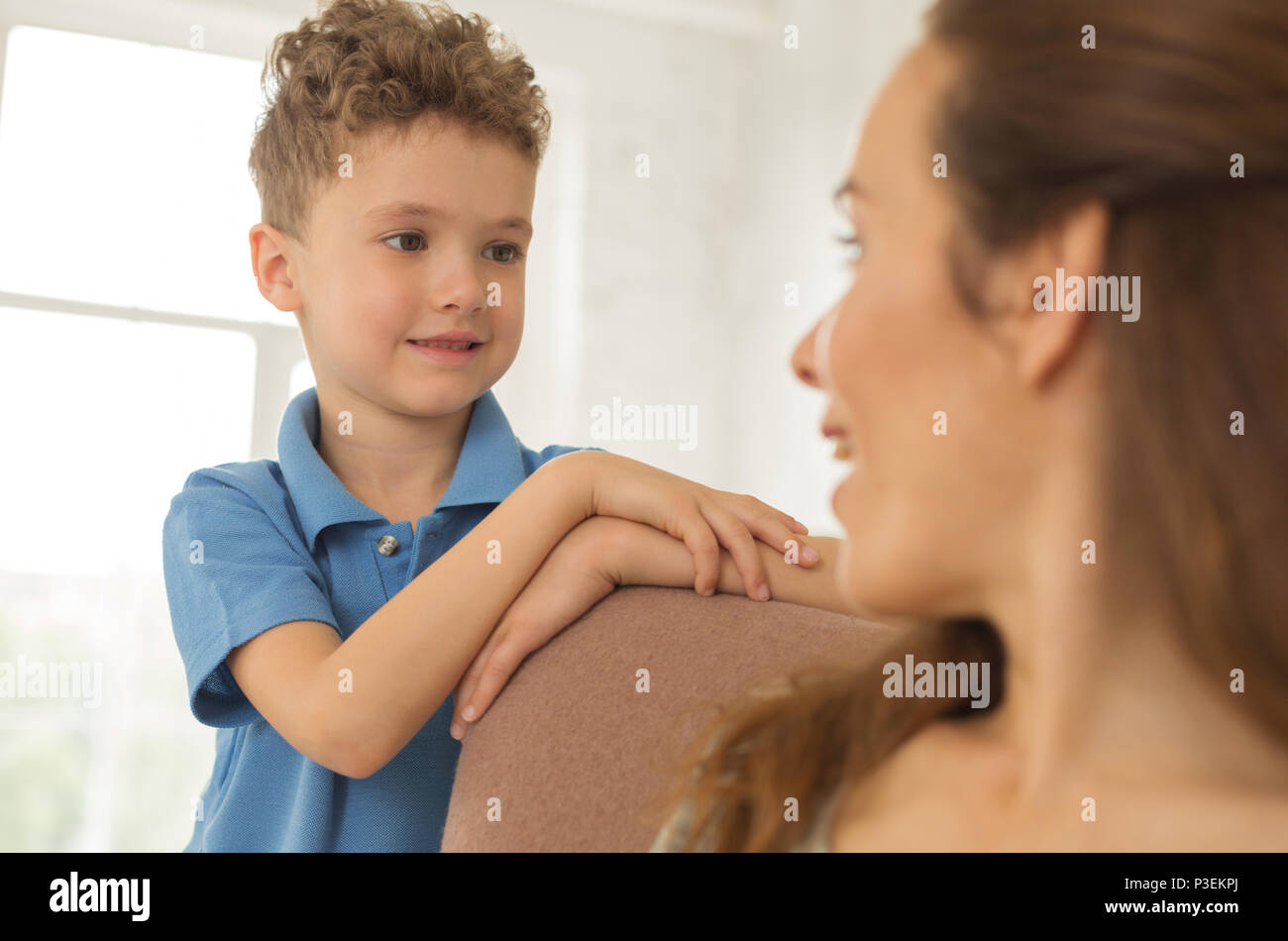 Little obedient son listening to his beautiful mother - Stock Image