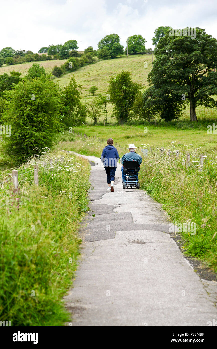 A woman and a man in wheelchair on a path which is on the bed of an old railway, Manifold Valley Staffordshire England UK - Stock Image