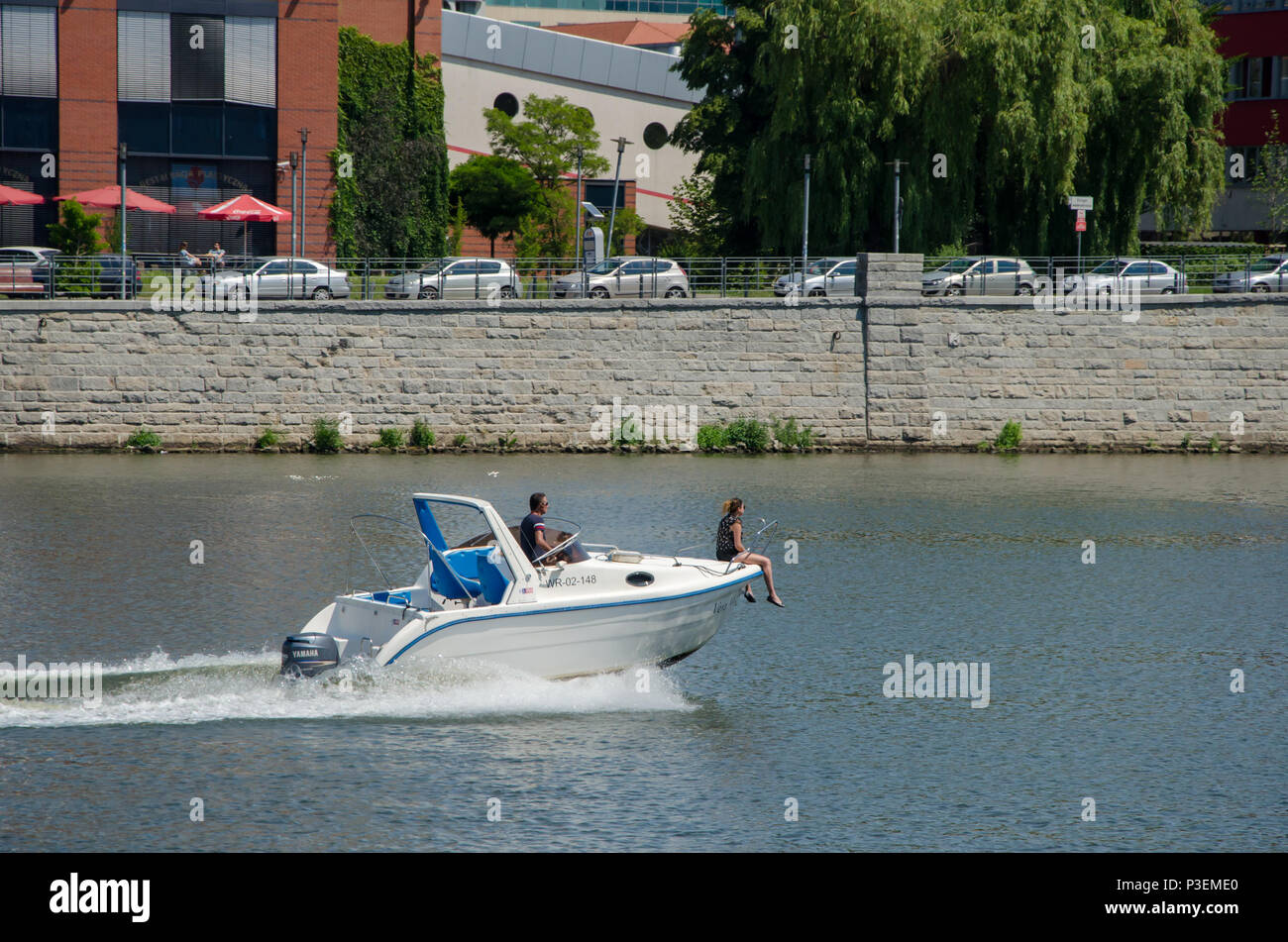 A couple in a motor boat in the river. Woman sit on rostrum of a boat. Poland, Wroclaw - Stock Image