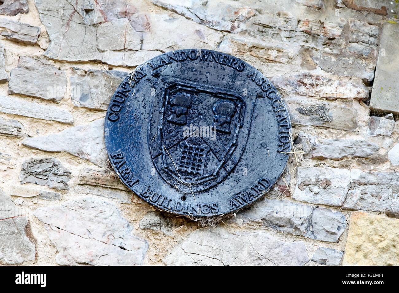A Country Landowners Association Farm Buildings Award plaque on a stone farm building, Staffordshire, England, UK - Stock Image