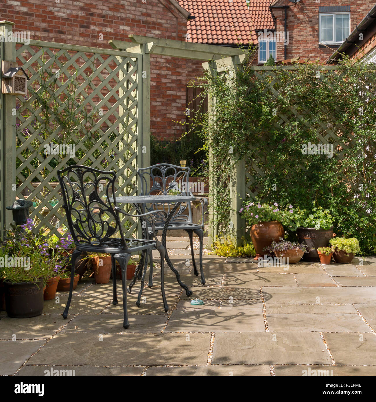 Small domestic garden patio with metal table and chairs, natural ...