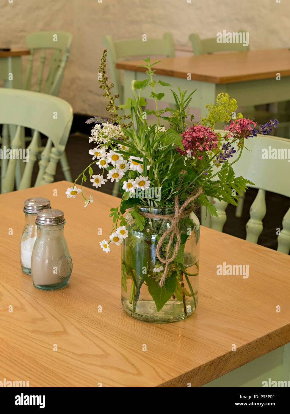 Simple Small Flower Arrangement In Glass Jam Jar Used As Table Decoration In Cafe Stock Photo Alamy
