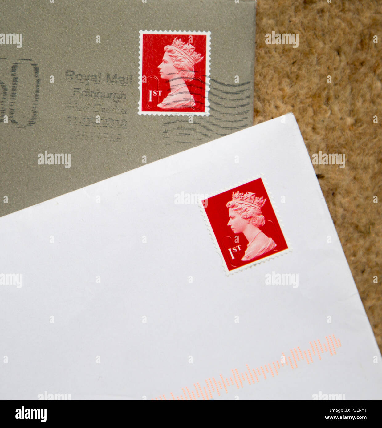 Looking down at letters in envelopes with red First class postage stamps, England, UK
