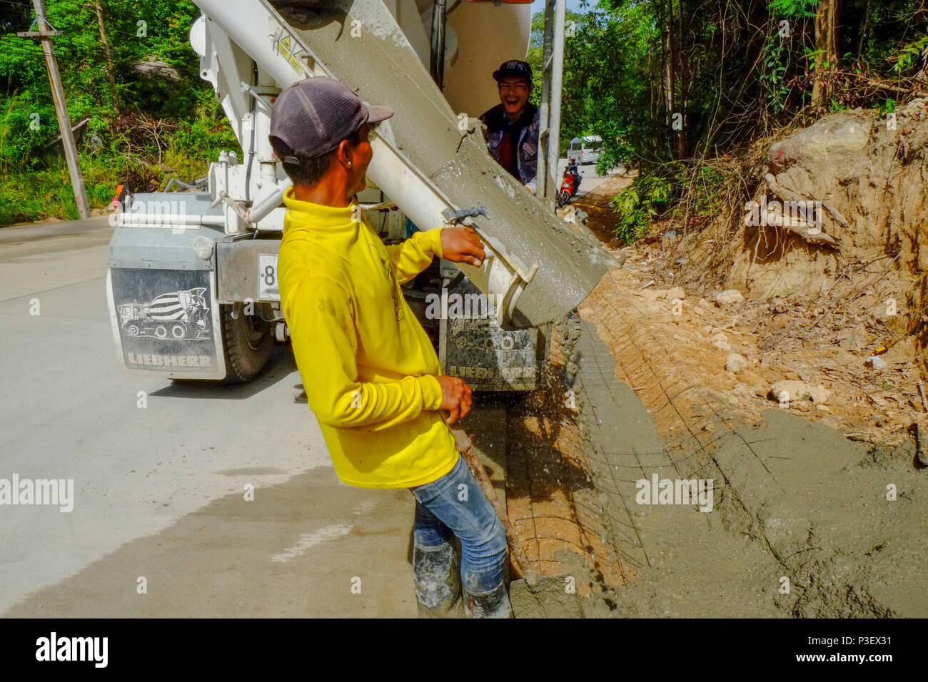 Construction Workers from Myanmar are building new roads through the jungles covering the mountains of the Thai island Koh Phangan, Thailand - Stock Image