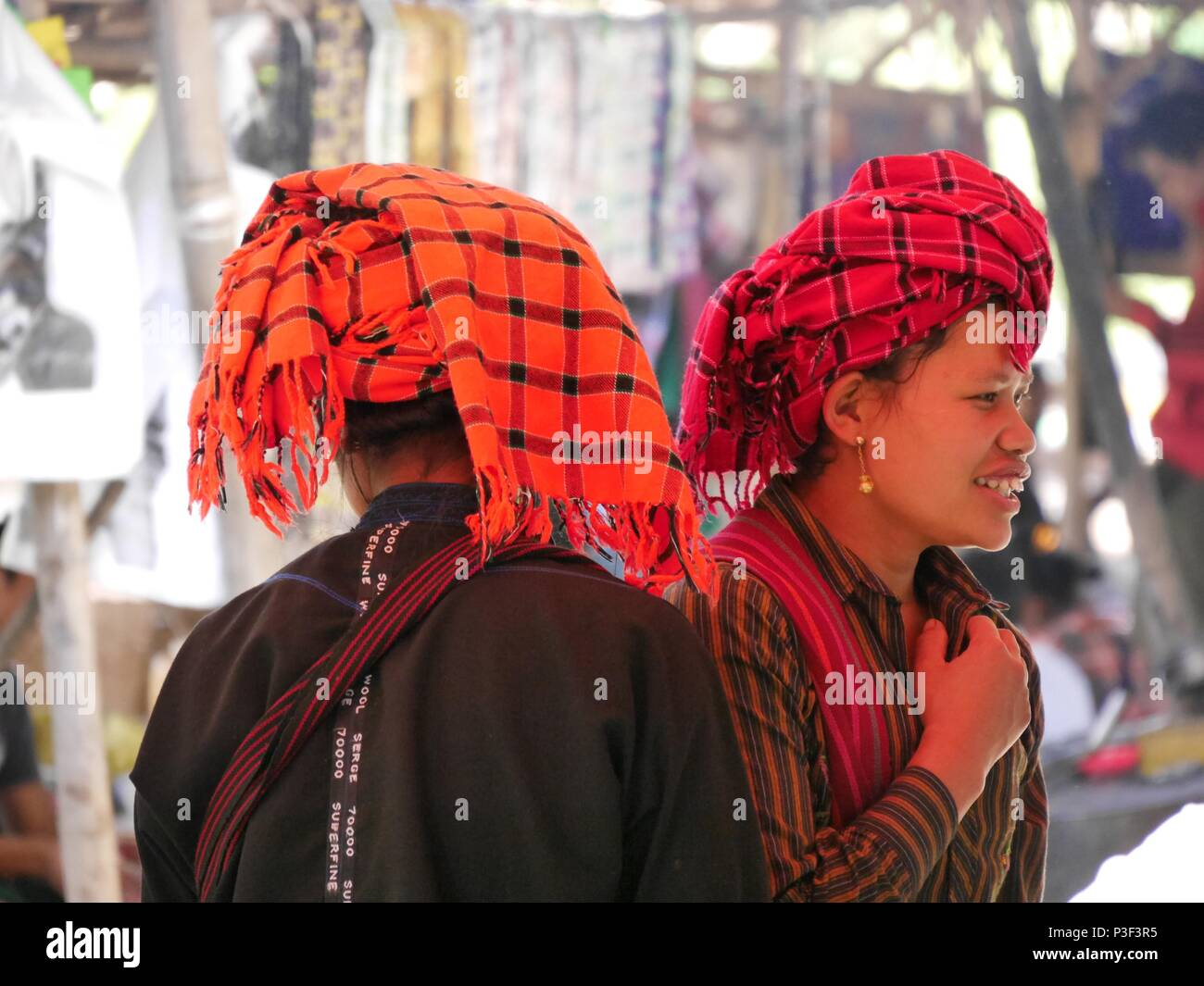 Close up of two smiling young Shan girls in bright red and orange checked traditional headdress in market near Inle Lake, Myanmar (Burma) - Stock Image