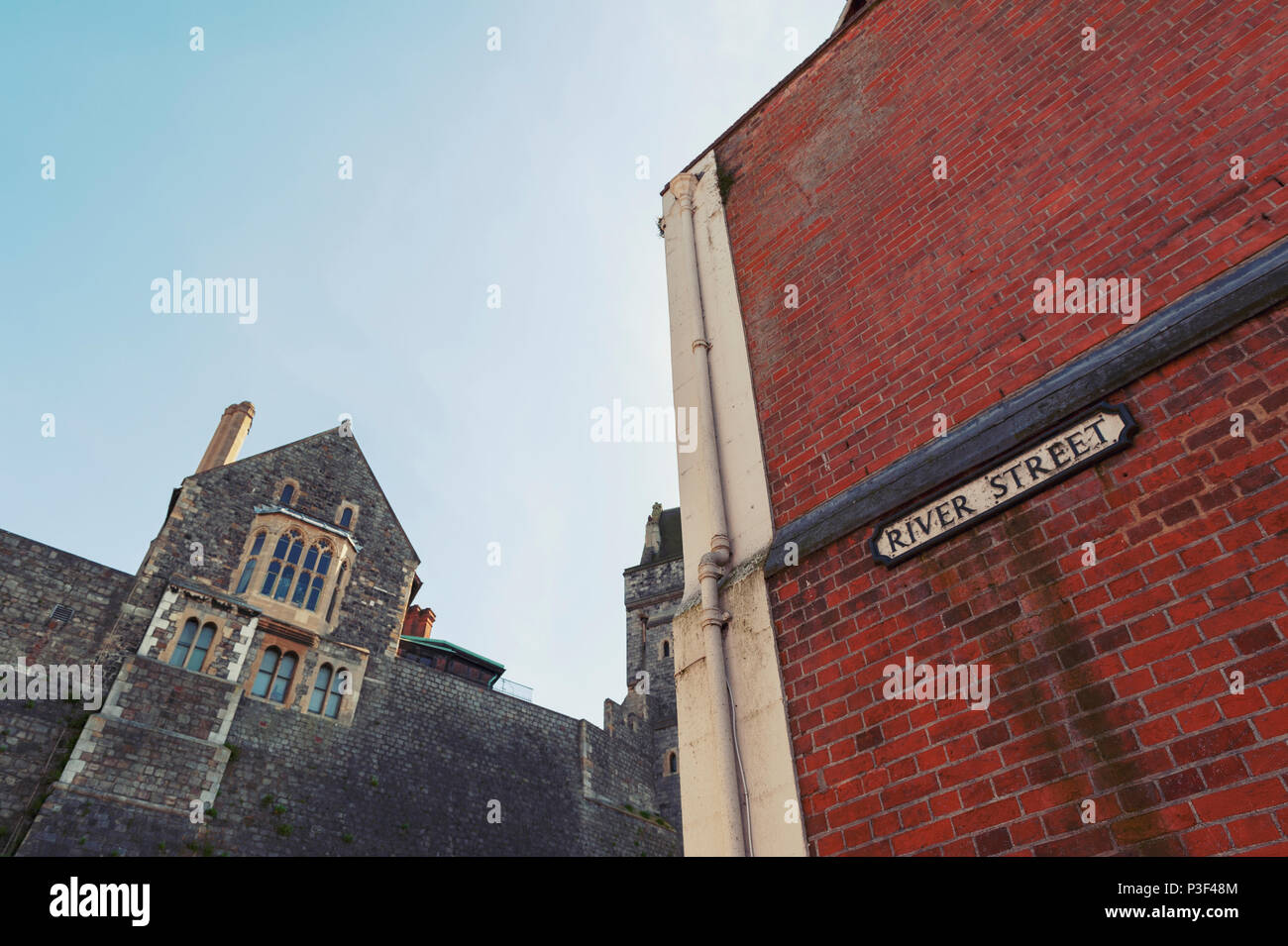 Corner Of Berkshire.Low Angle Shot Of Ancient Stone Buildings And Red Brick Wall