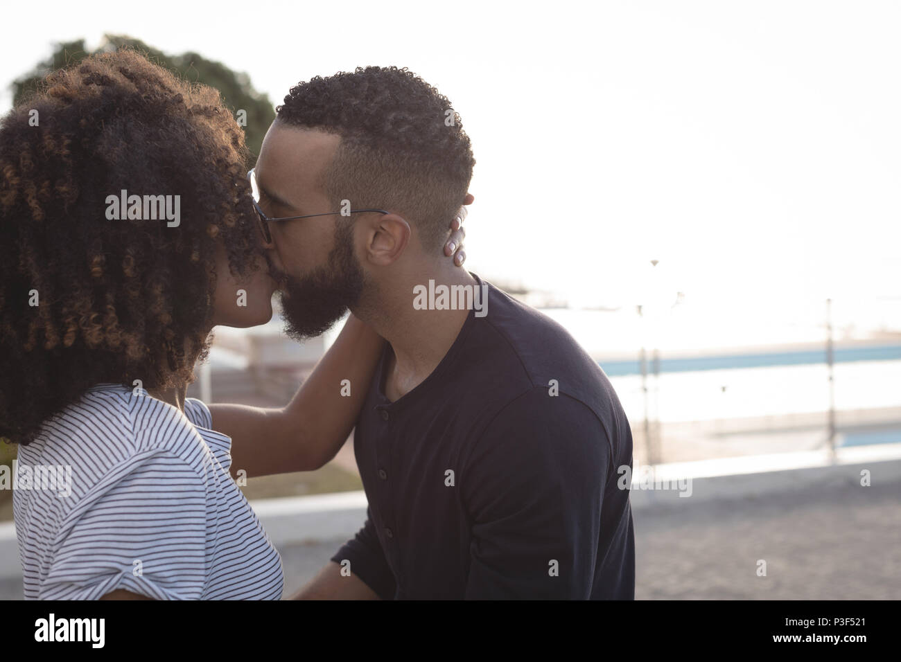 Couple kissing each other near beach - Stock Image