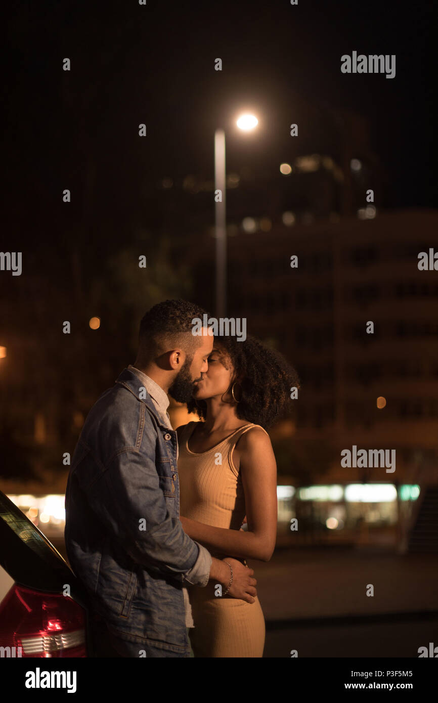 Couple kissing each other on road - Stock Image