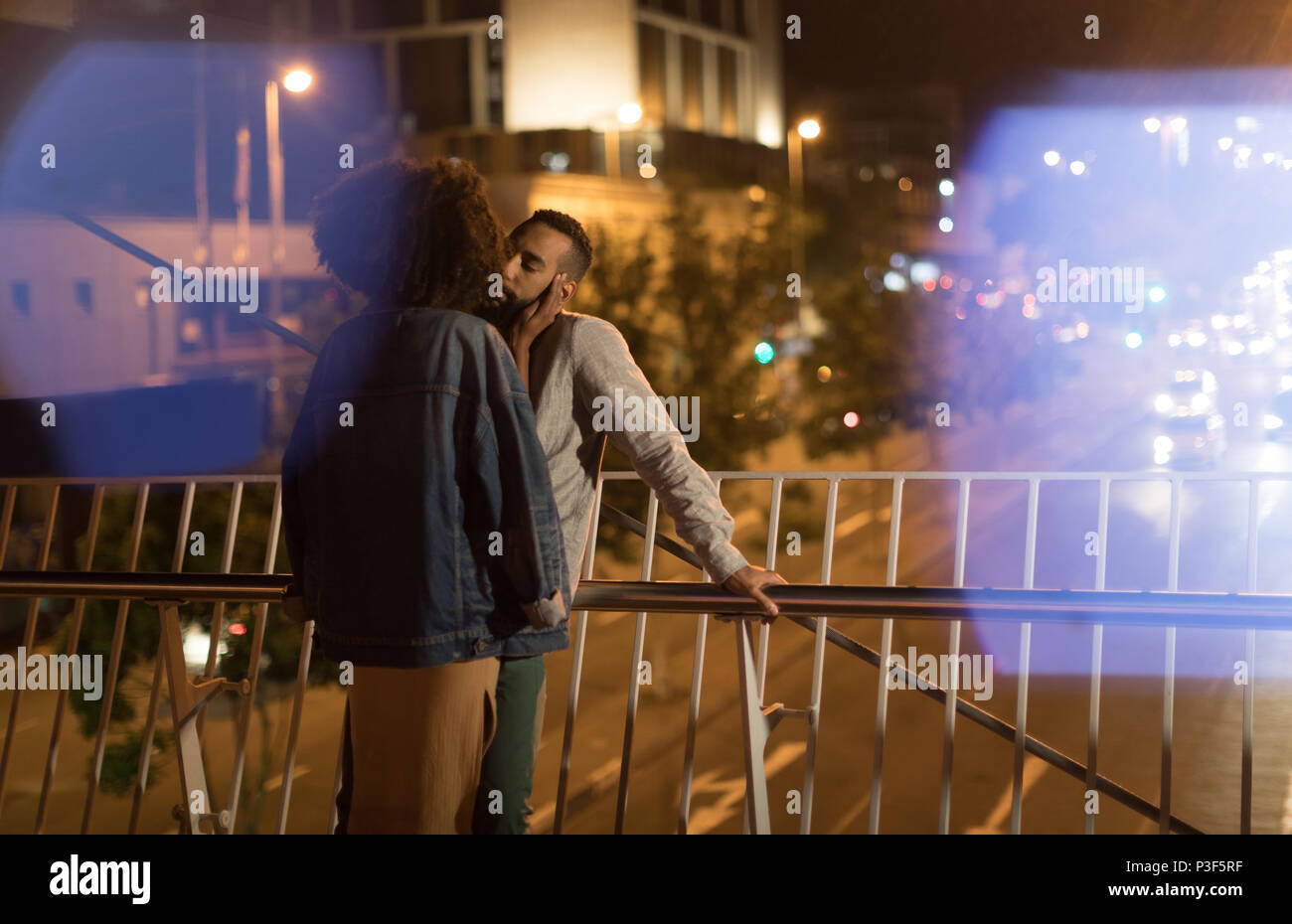 Couple kissing each other while standing near railing - Stock Image