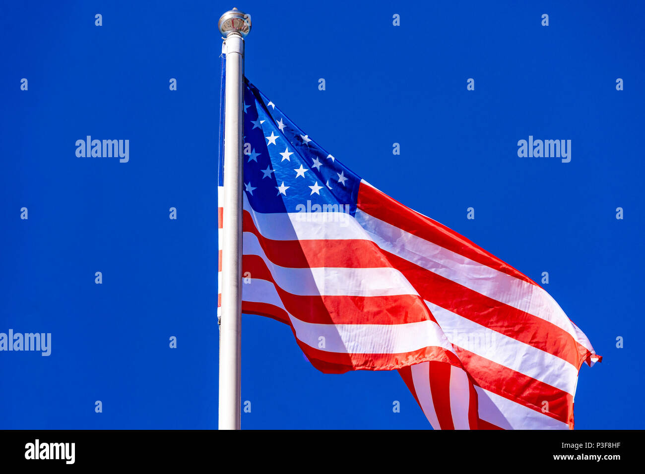 American Flag against blue sky. Stock Photo