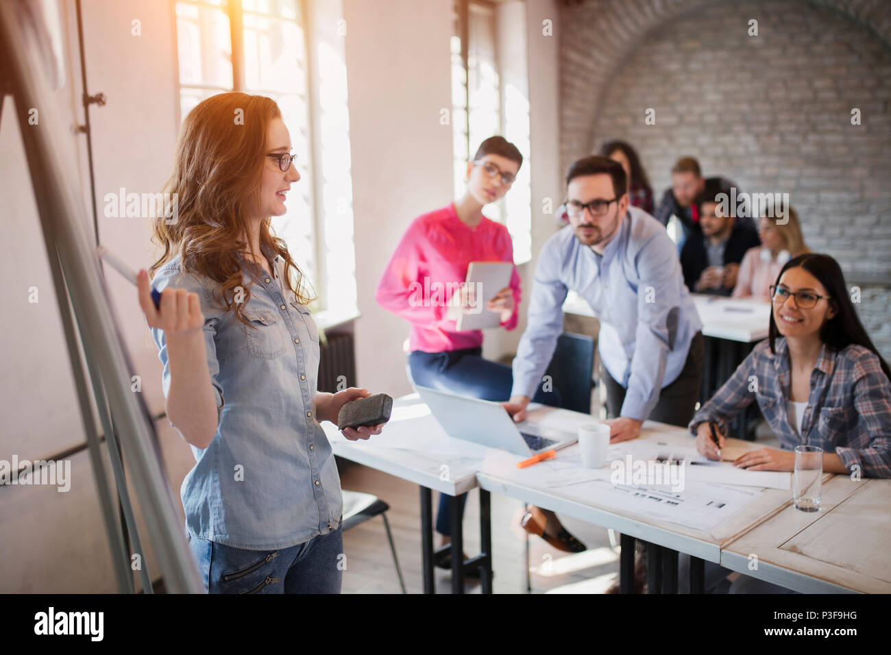 Picture of architect doing presentation to her colleagues - Stock Image