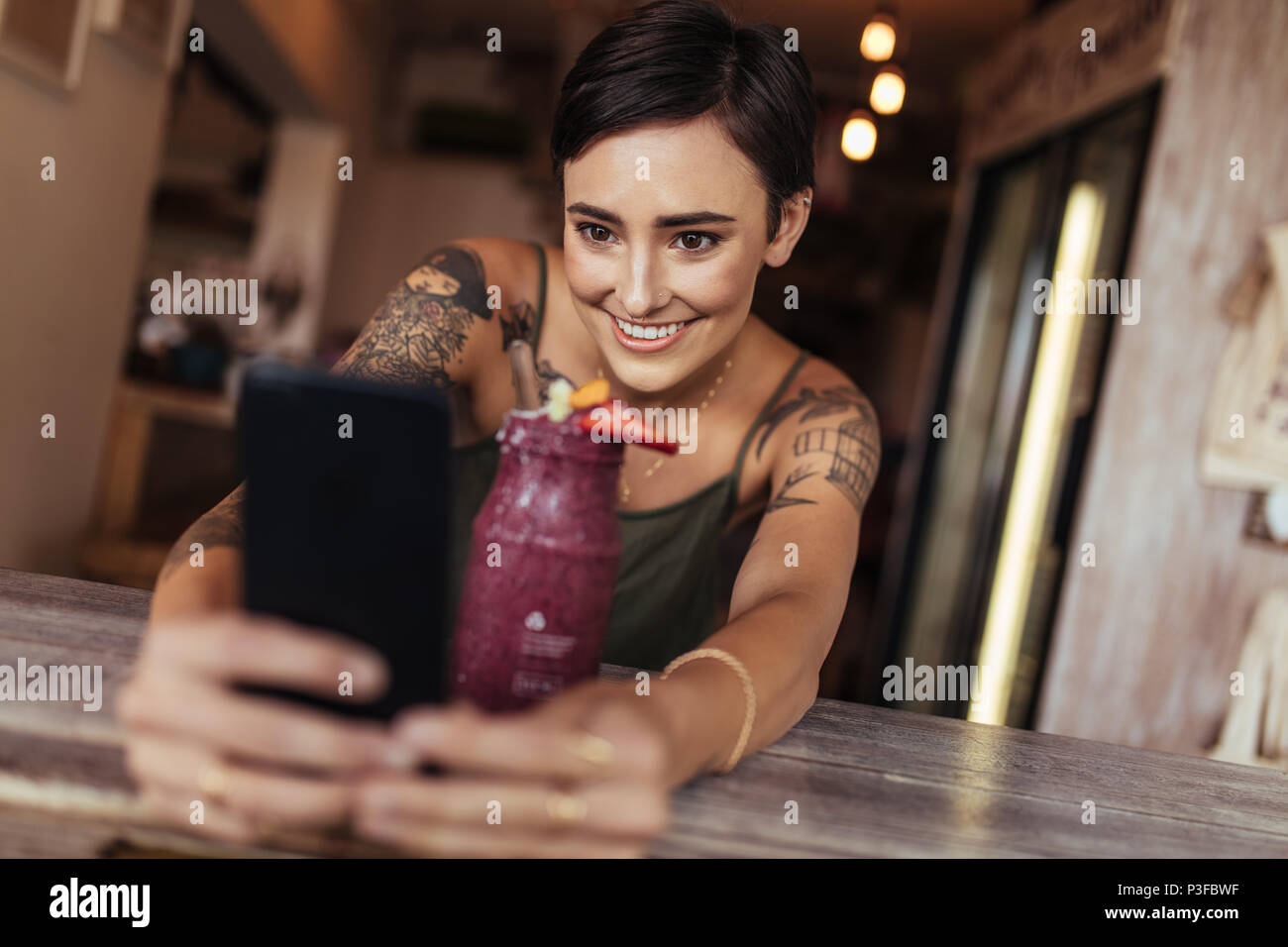 Smiling woman taking a selfie with a smoothie placed in front of her using a mobile phone for her food blog. Food blogger shooting photos for her blog - Stock Image