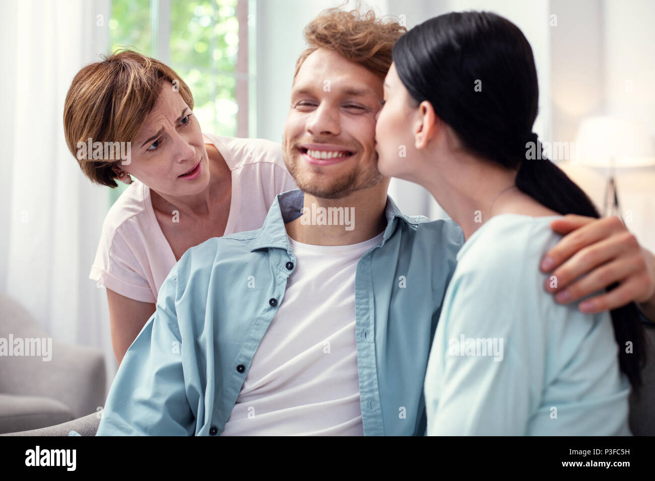 Unhappy aged woman looking at the couple Stock Photo