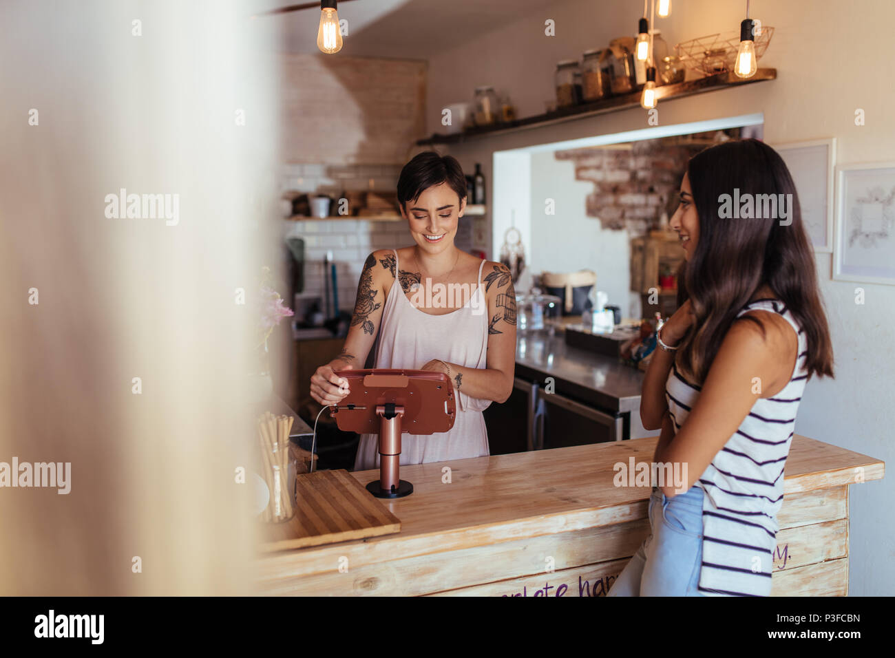 Woman standing at the billing counter of her cafe accepting orders. Woman ordering food across the counter at a restaurant. - Stock Image