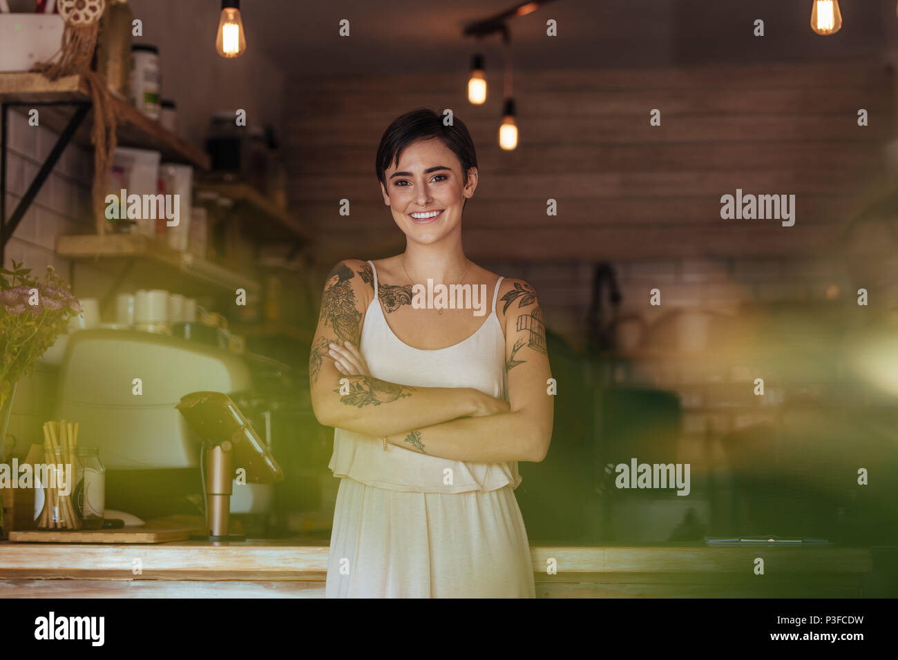 Woman standing in front of the counter of her cafe with folded arms. Smiling restaurant owner posing for a photograph at the billing counter. - Stock Image
