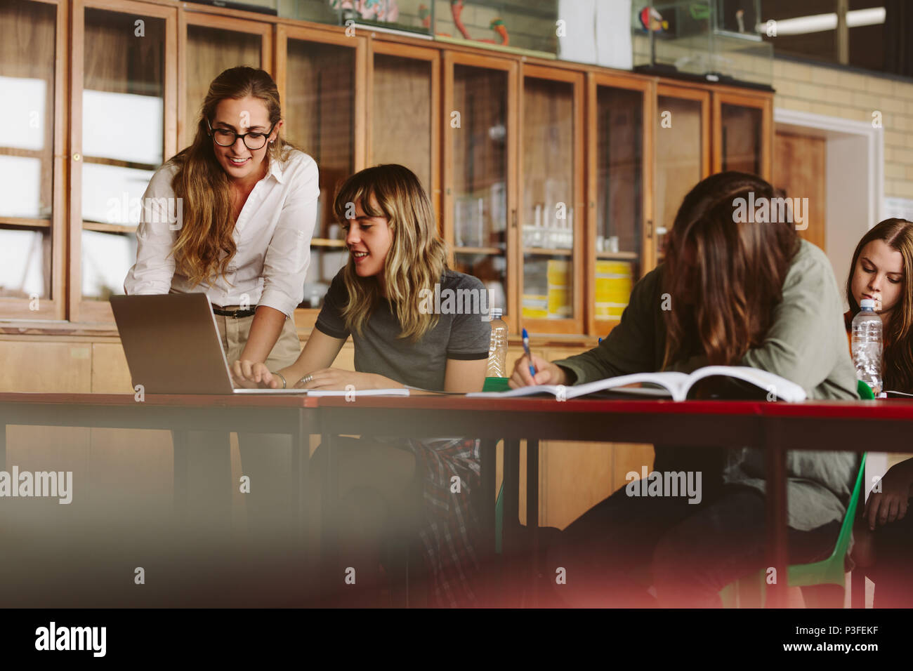 Happy young teacher helping a female student  studying on laptop in classroom. Professor assisting students in lecture. - Stock Image