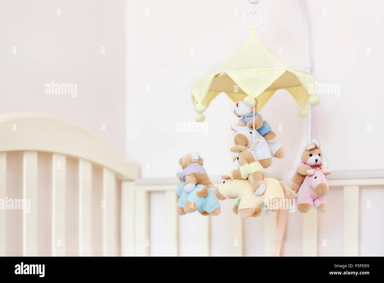 Close-up baby crib with musical animal mobile at nursery room. Hanged developing toy with plush fluffy animals. Happy parenting and childhood, expecta - Stock Image