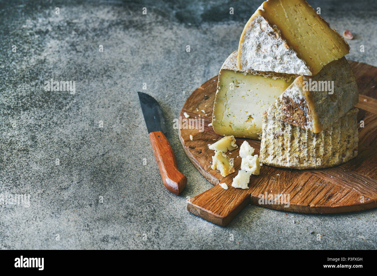 Cheese assortment on wooden board, copy space Stock Photo