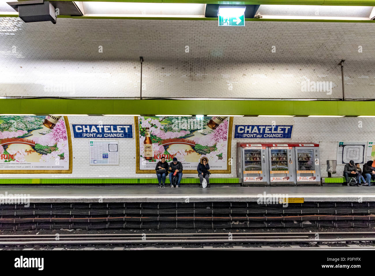 People sitting waiting for a train on Châtelet Pont Au Change station on The Paris Metro ,France - Stock Image