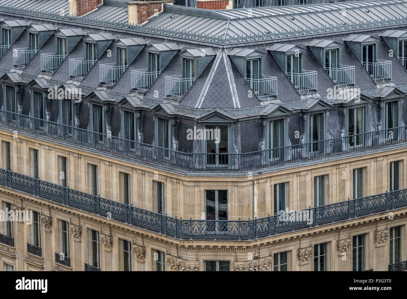 The  elegant  grey slate rooftops of Paris apartment buildings a running balcony and attic rooms, Boulevard Haussmann ,Paris ,France - Stock Image