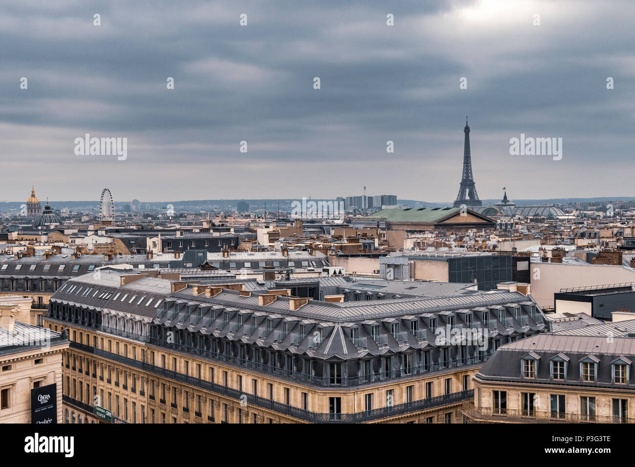 The Eiffel Tower and elegant  grey slate rooftops of Paris apartment buildings a running balcony and attic rooms, Boulevard Haussmann ,Paris ,France - Stock Image