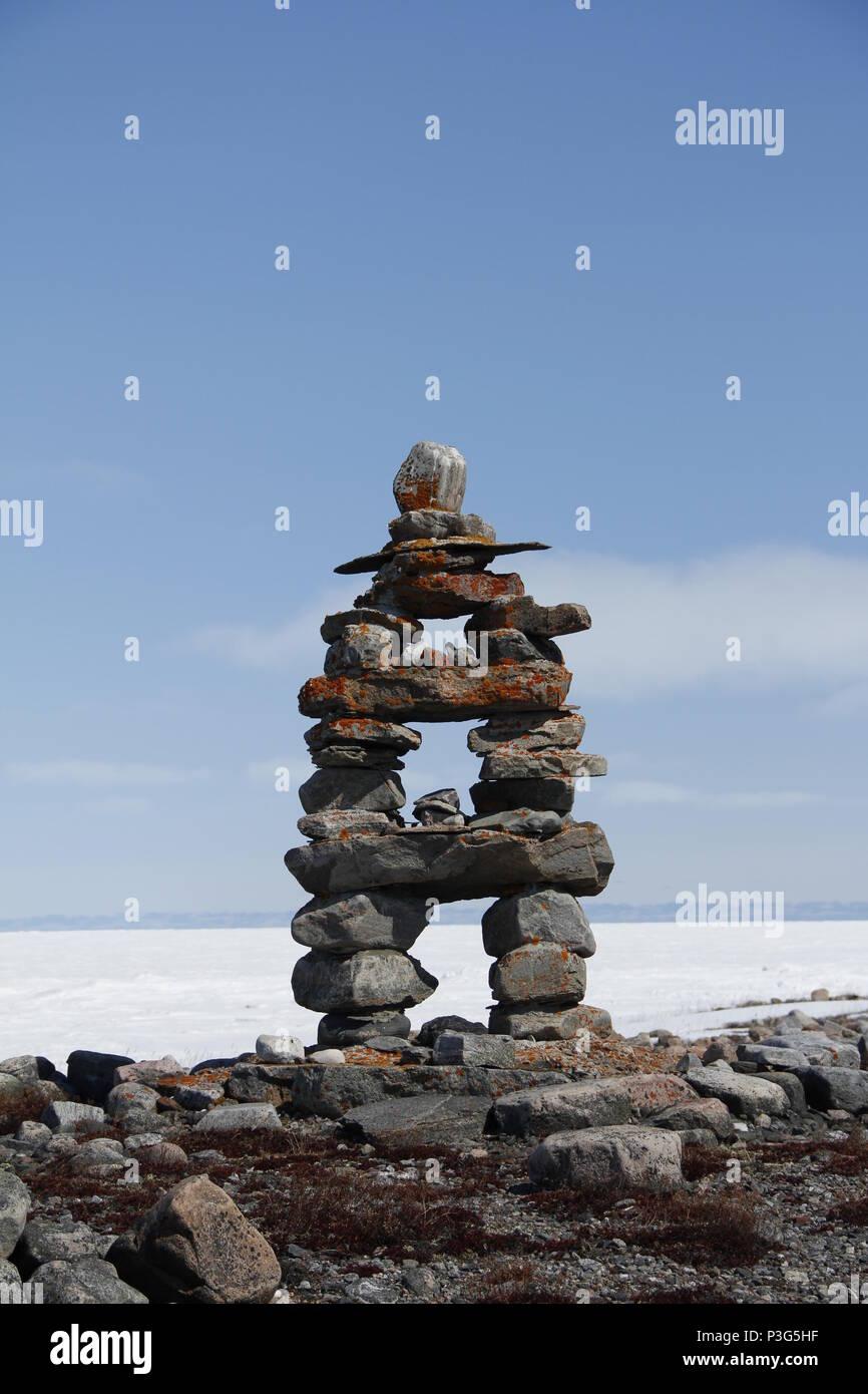 Inukshuk or Inuksuk landmark with frozen bay in the background near Arviat, Nunavut - Stock Image