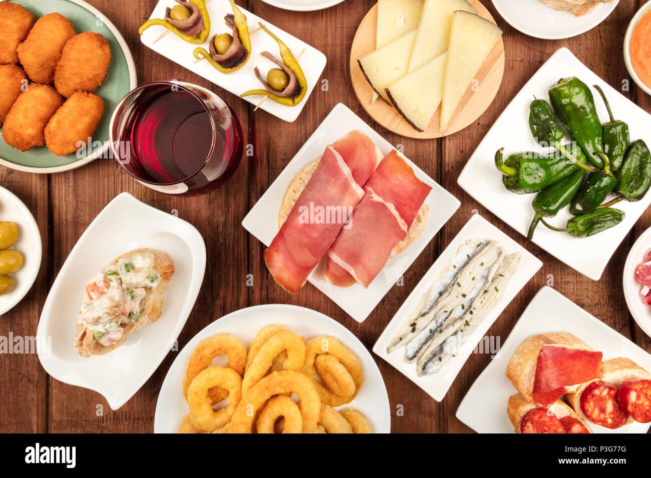 The food of Spain. An overhead photo of various Spanish tapas, shot from above on a dark rustic texture. Jamon, cheese, wine, olives, croquettes, cala - Stock Image