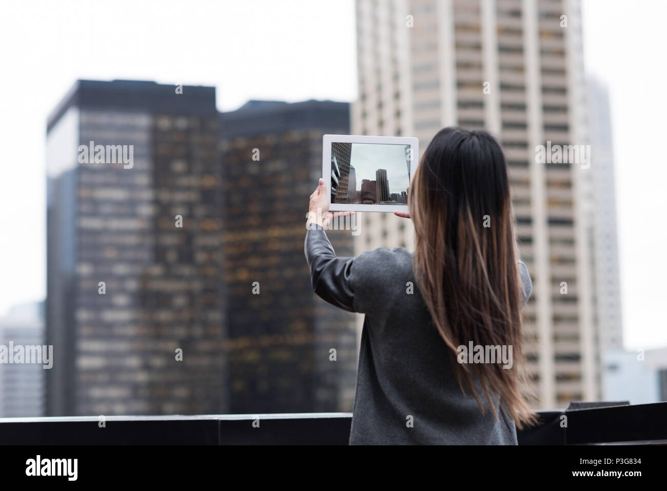Businesswoman photographing skyscrapers with her tablet - Stock Image