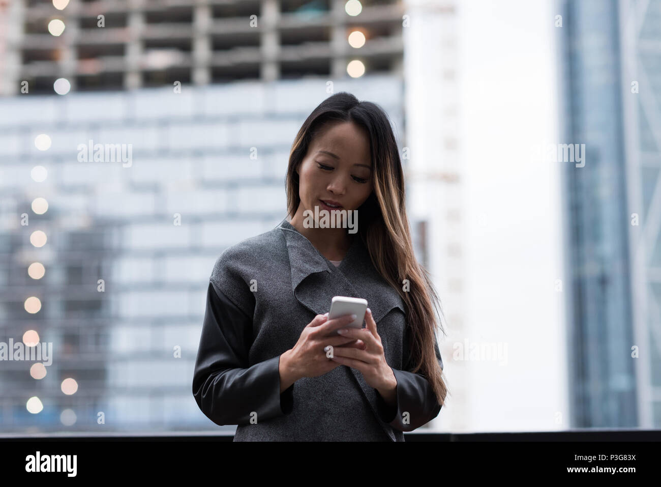 Businesswoman using her mobile phone - Stock Image