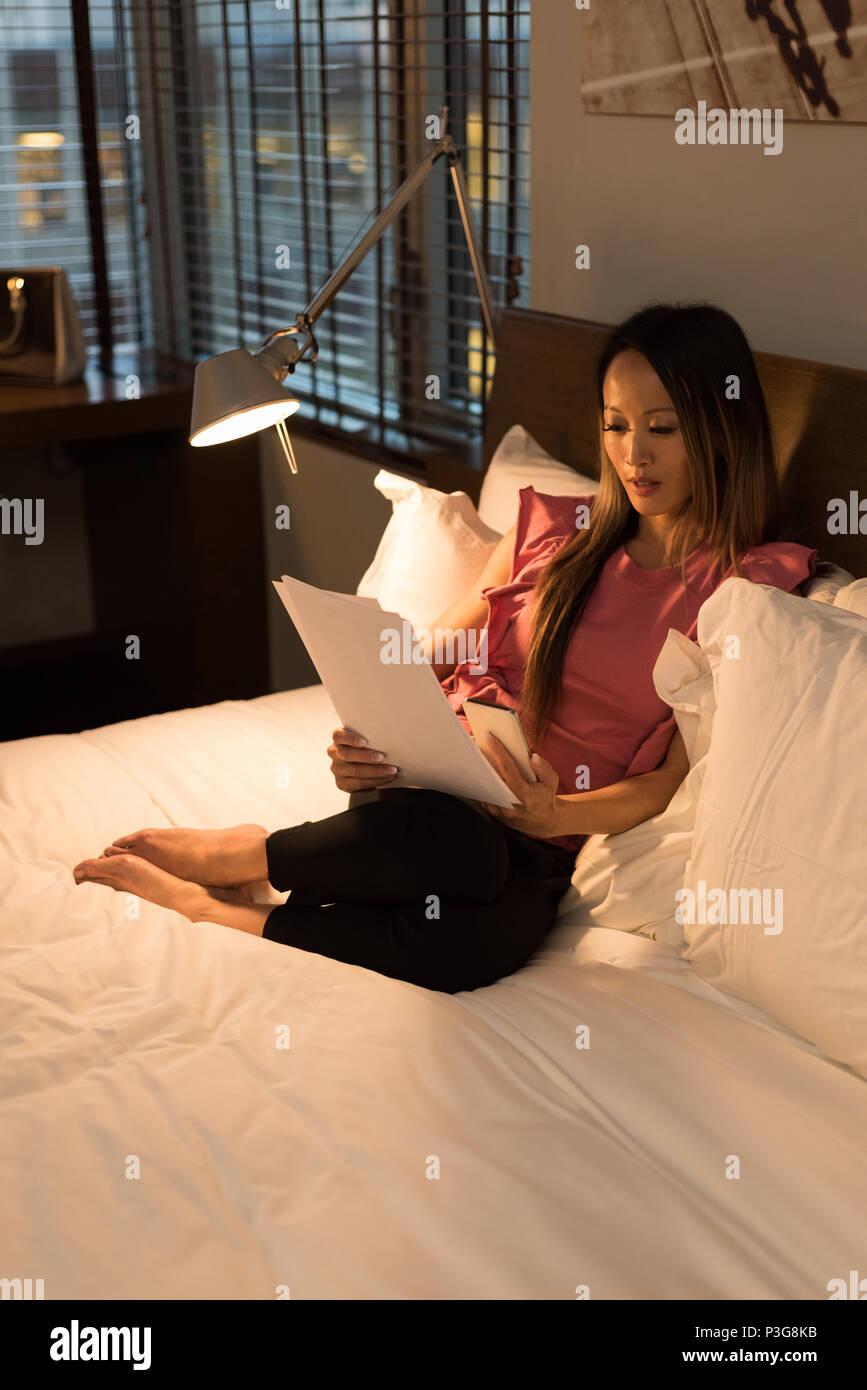 Businesswoman sitting on bed reading documents - Stock Image