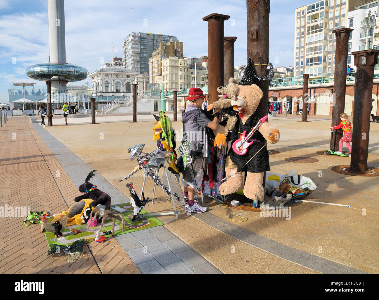 An eccentric street performer / busker on Brighton seafront with his weird and wonderful 'bandmates', East Sussex, England, UK - Stock Image