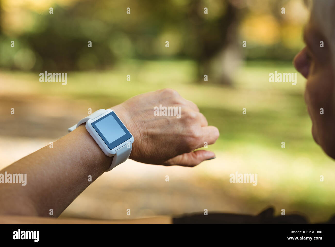 Senior woman using a smart watch in a park on a sunny day - Stock Image