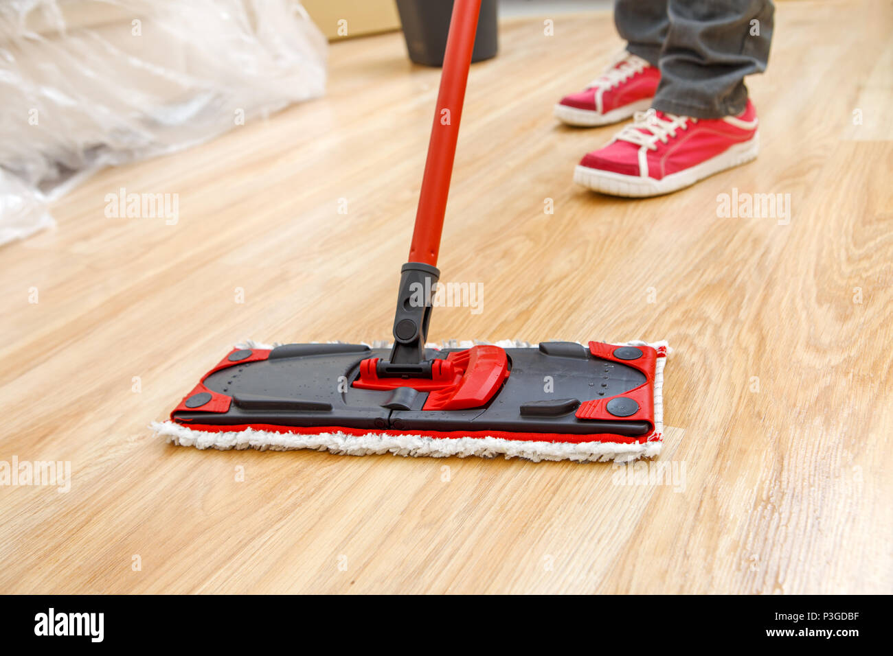 Photo of man's feet with mop washer floor - Stock Image