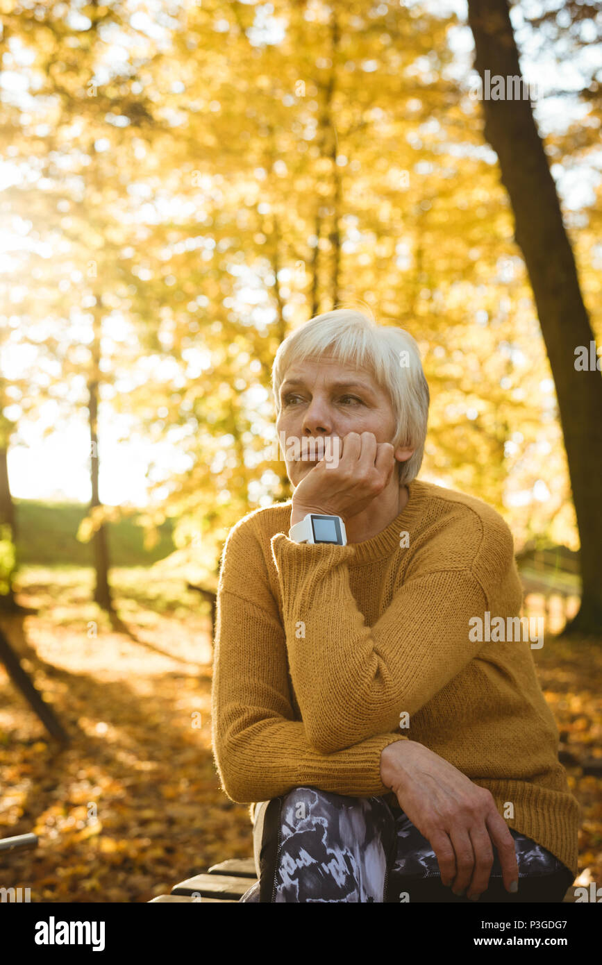 Thoughtful senior woman sitting in a park - Stock Image