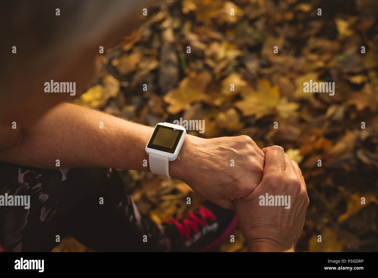 Senior woman using a smart watch in a park - Stock Image