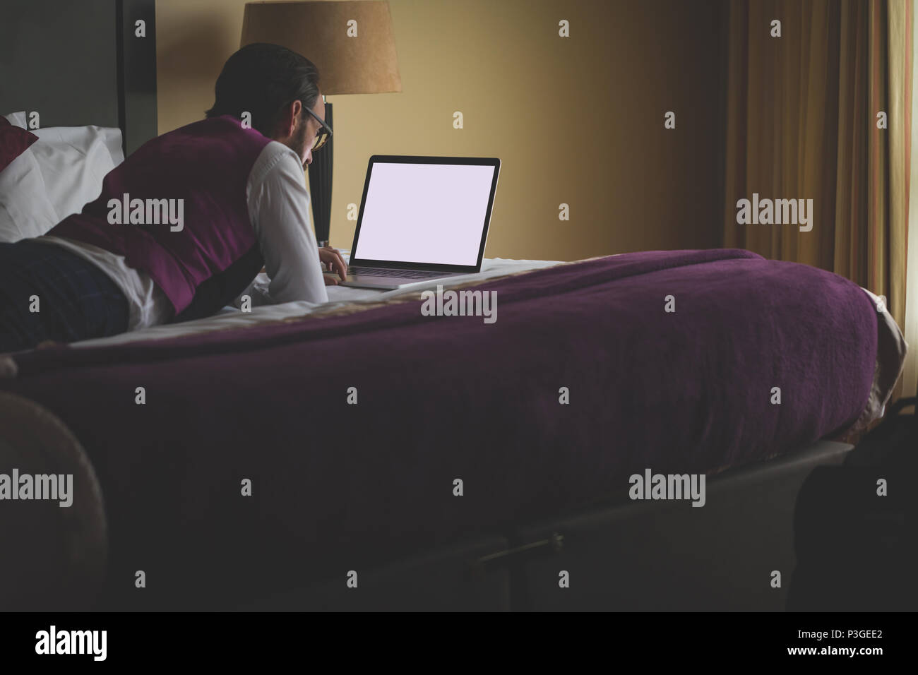 Businessman using laptop on bed - Stock Image