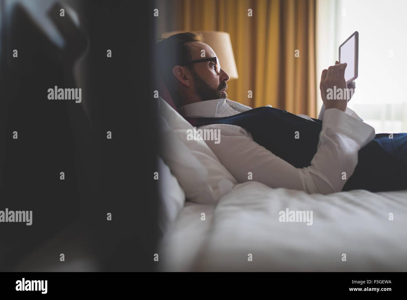 Businessman using digital tablet in bedroom - Stock Image