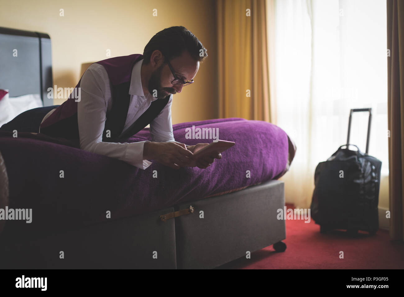Businessman using digital tablet on bed - Stock Image