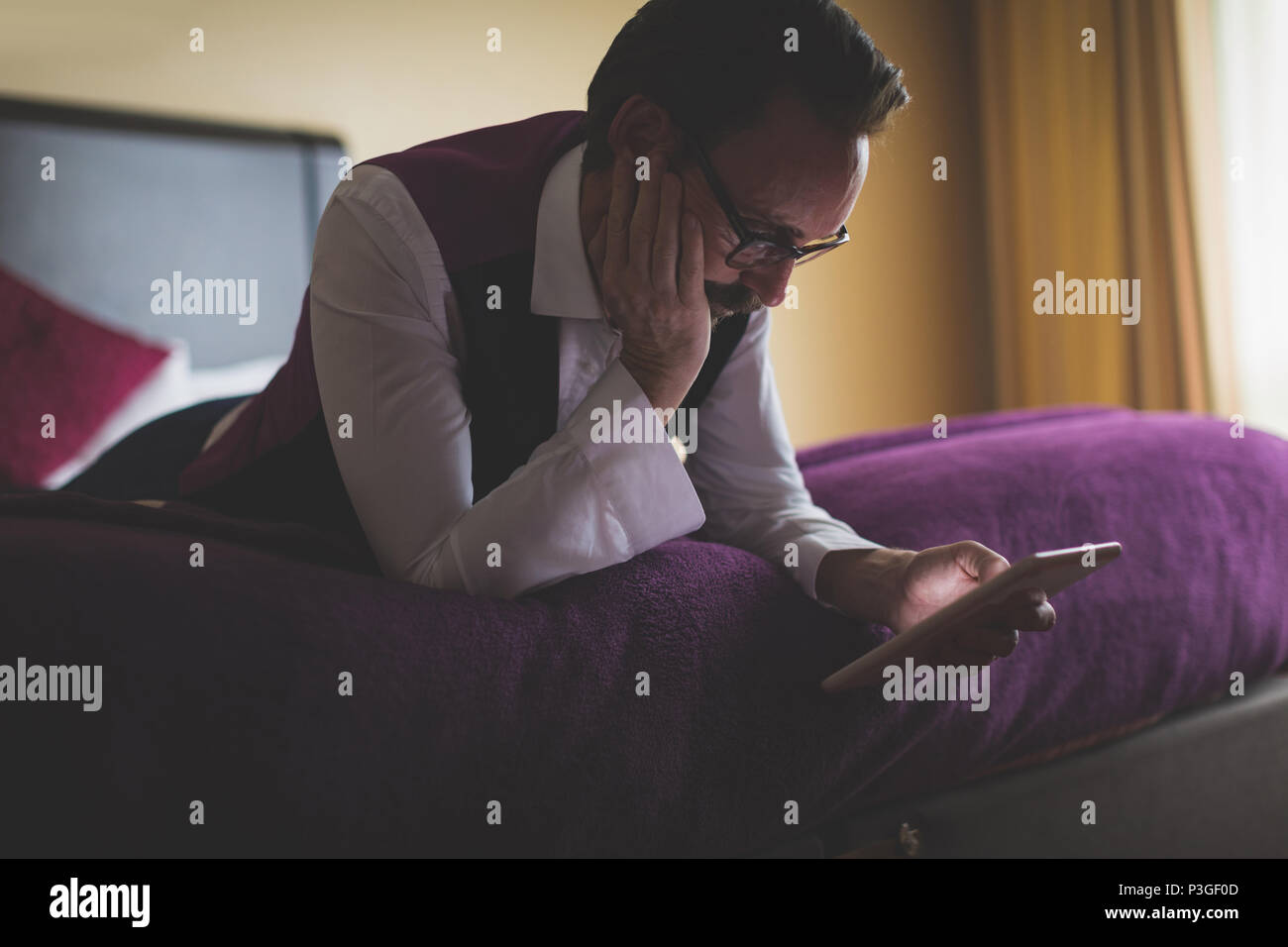 Businessman using digital tablet in bedroom - Stock Image