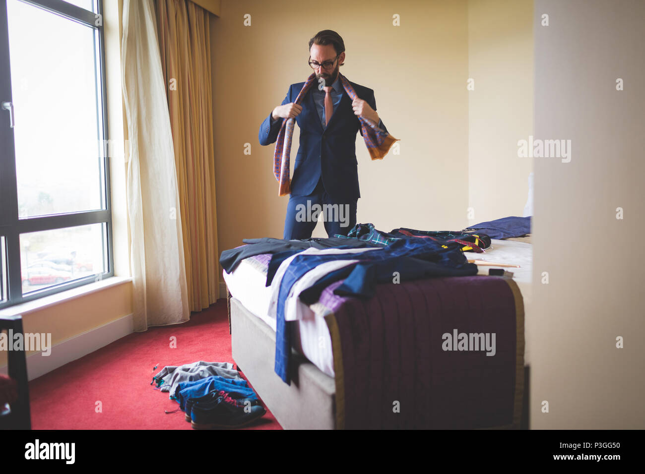 Businessman wearing his tie in hotel room - Stock Image