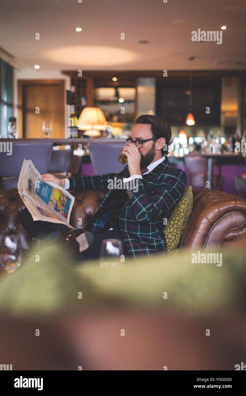 Businessman reading newspaper while having whisky - Stock Image