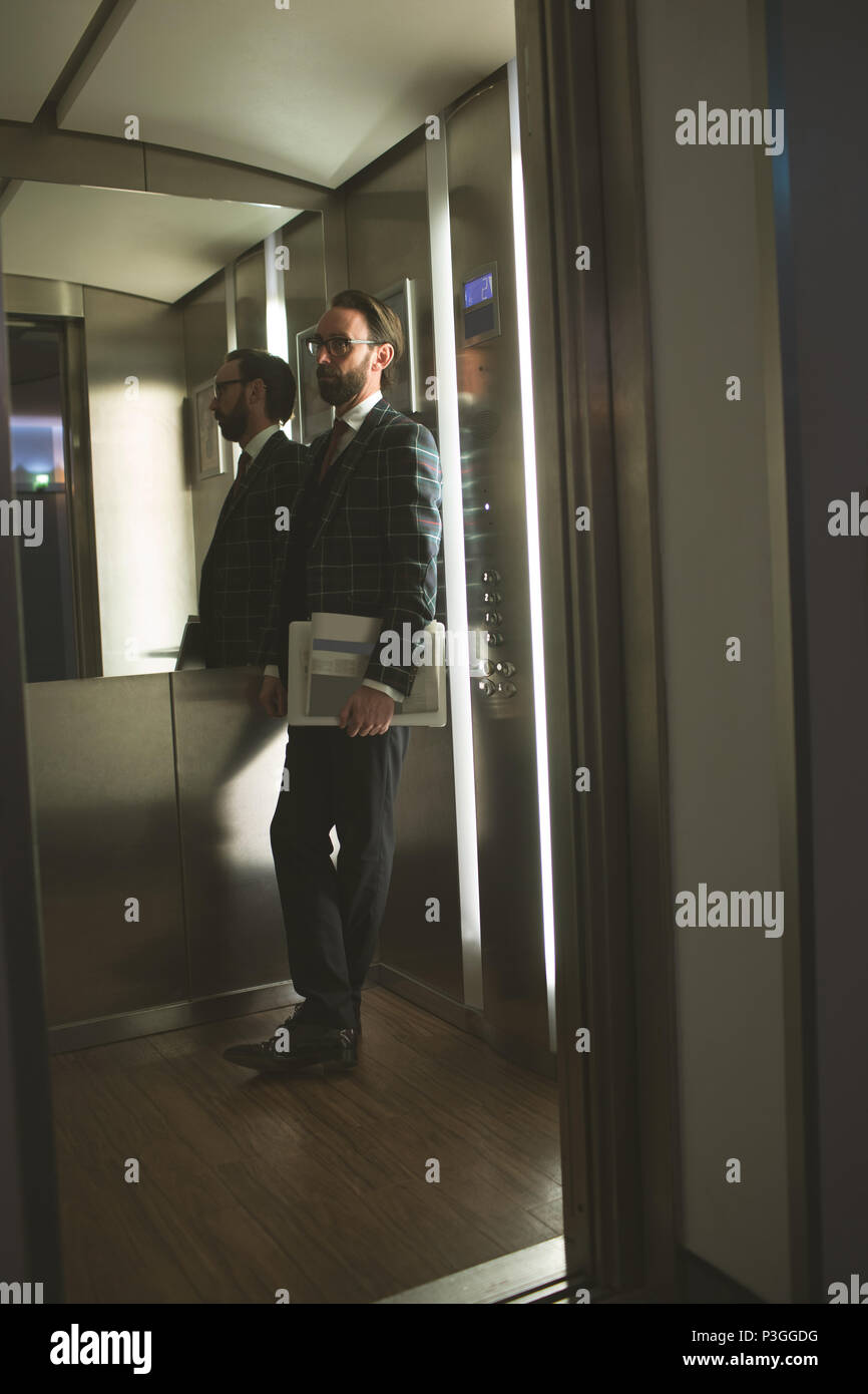 Businessman standing in the lift - Stock Image