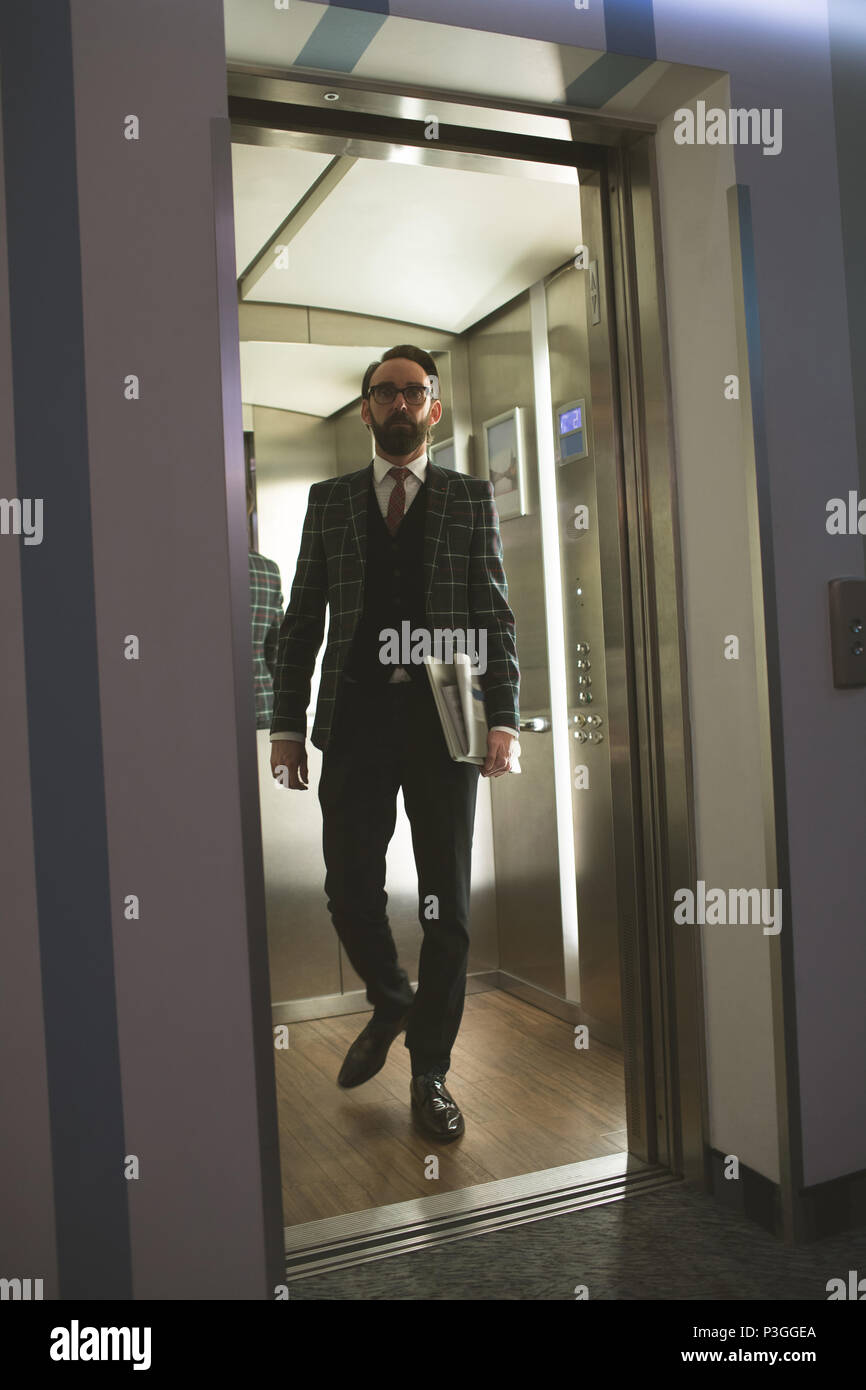 Businessman coming out of the lift - Stock Image