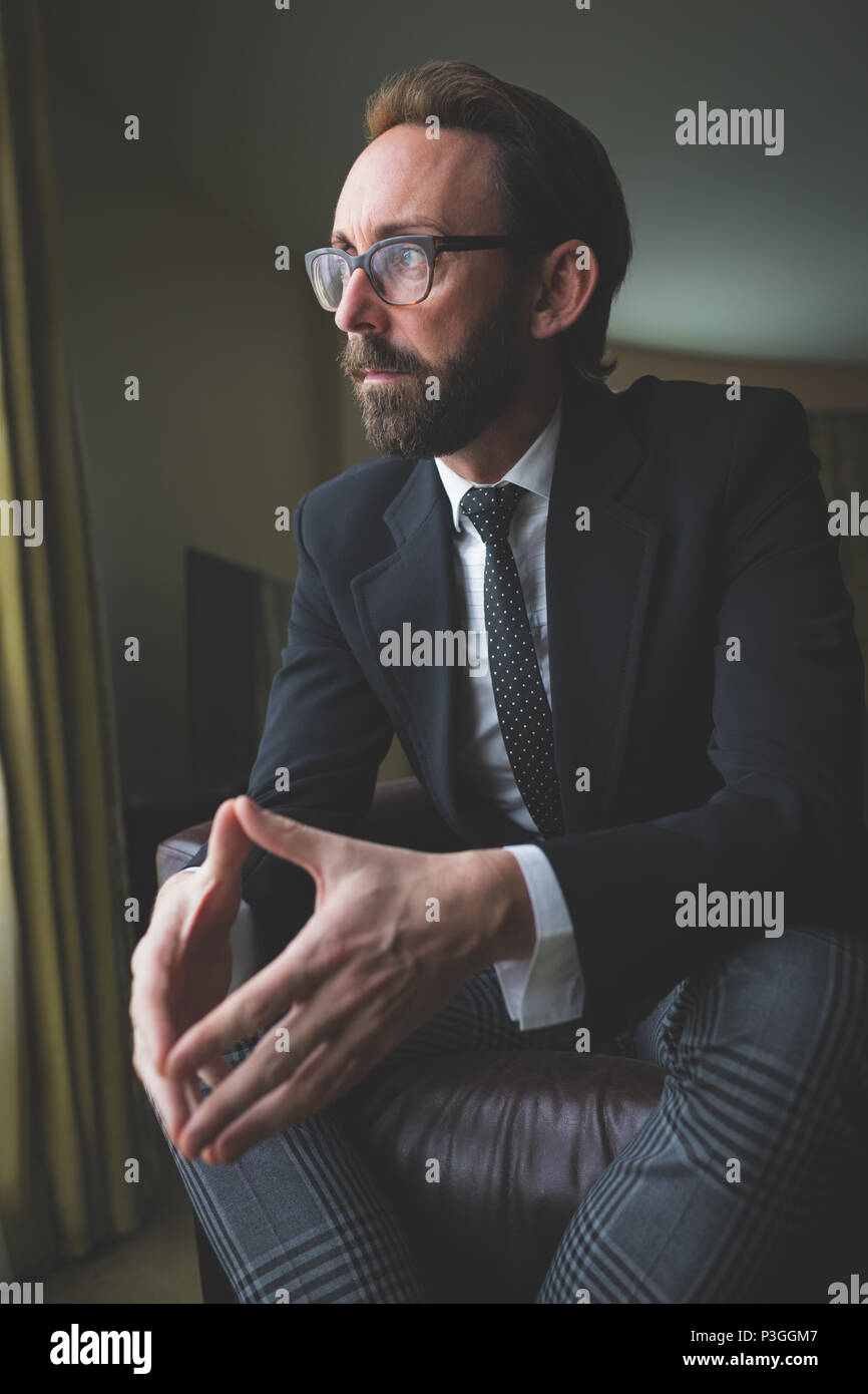 Thoughtful businessman sitting on arm chair - Stock Image