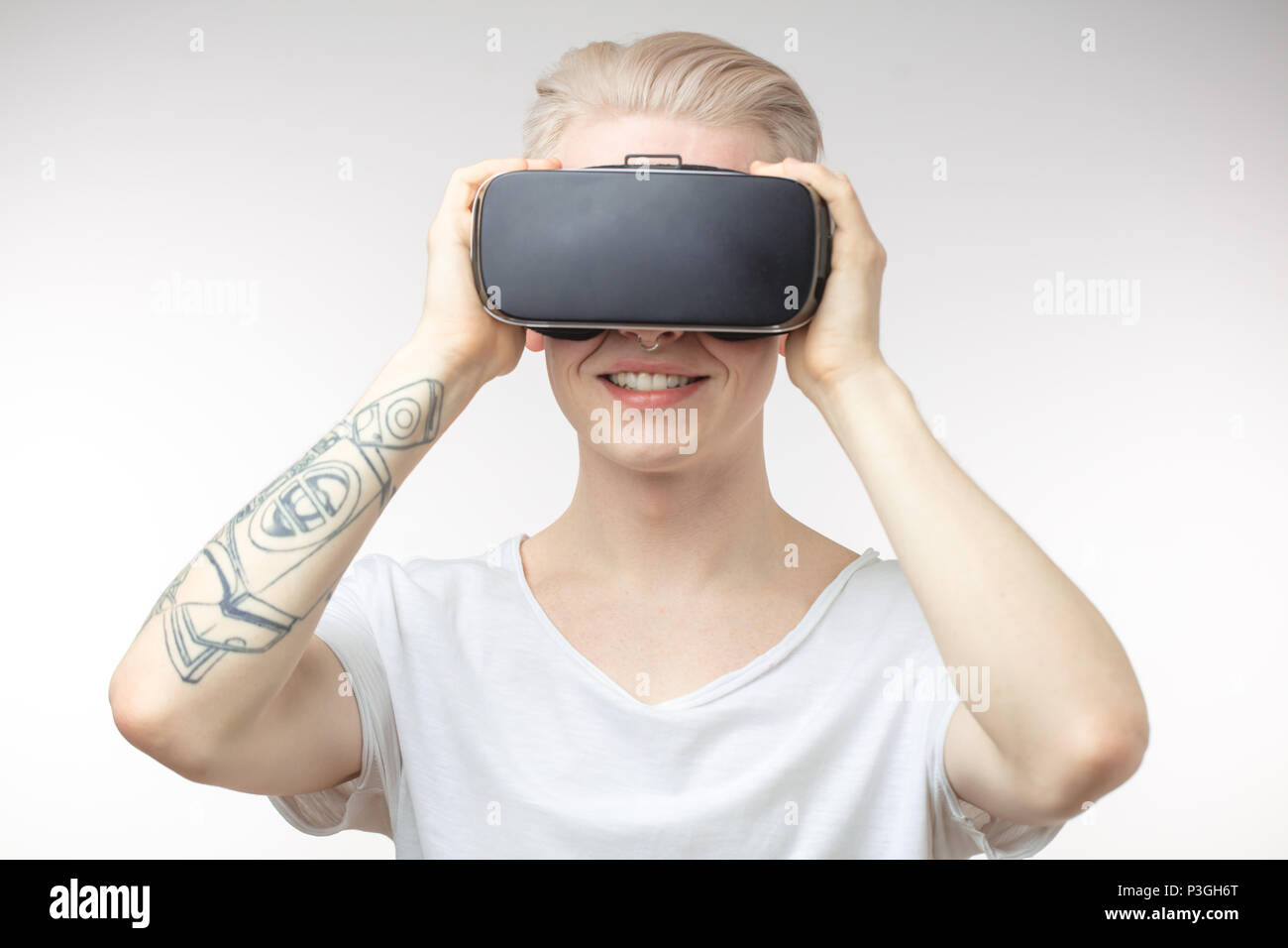 Blonde Man getting experience using VR headset glasses of virtual reality - Stock Image