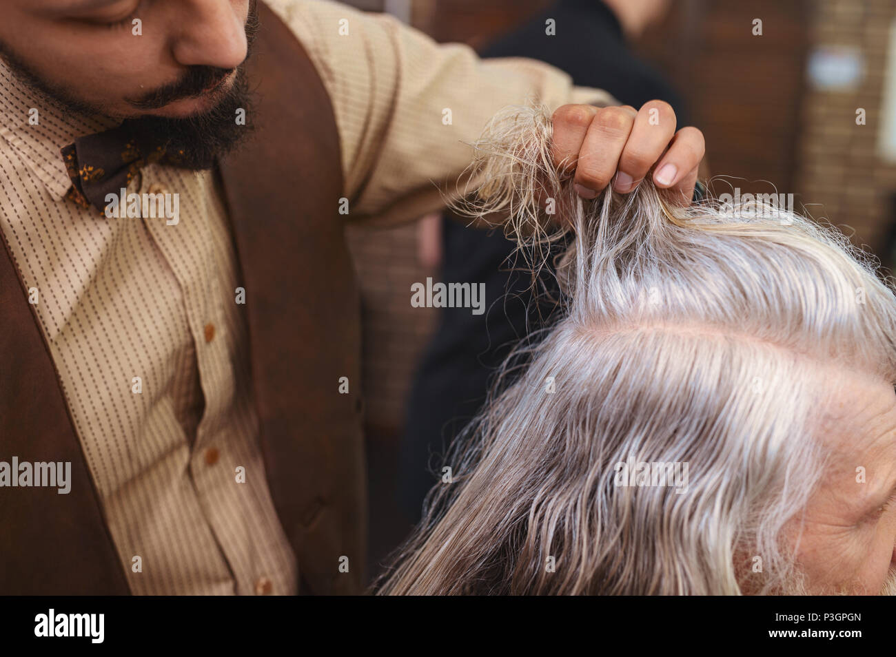 Close up of male hand that creating hairstyle - Stock Image