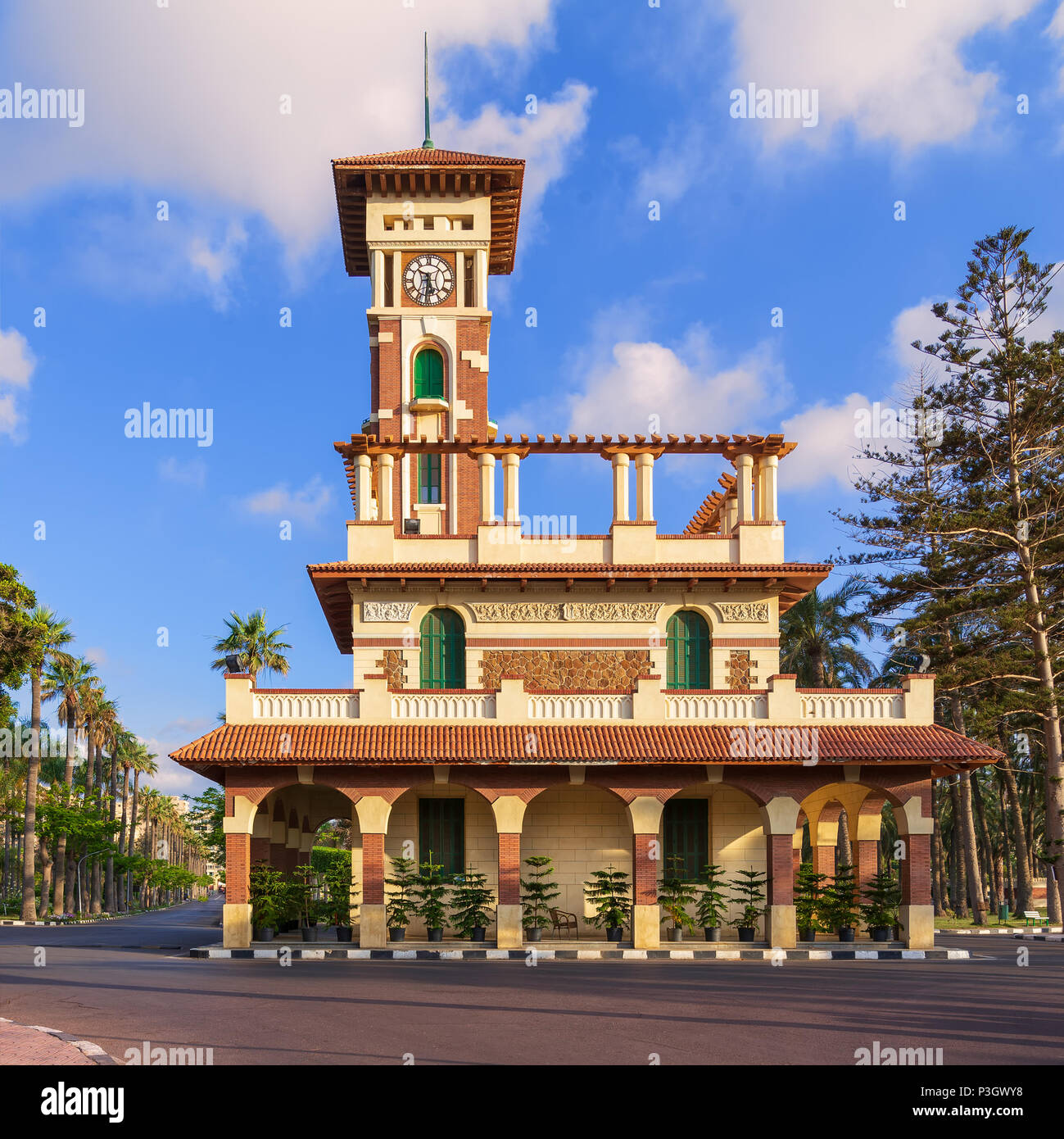 Facade of the clock tower in Montaza public park with decorated stone wall, green wooden window shutters, and red tile canopies after sunrise, Alexand - Stock Image