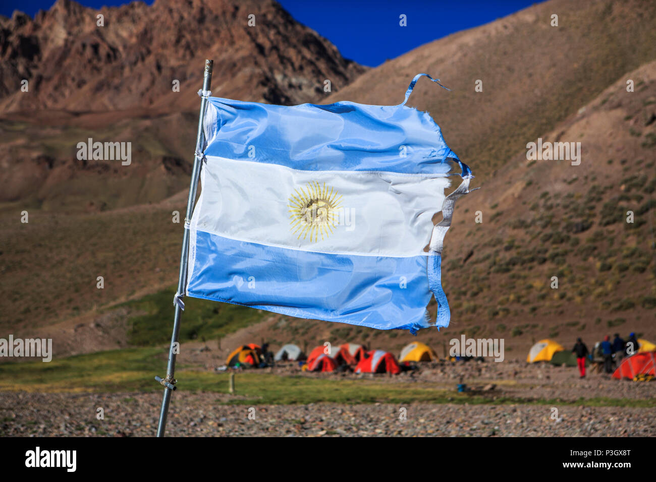 Argentinian flag waving in front of campsite on approach hike to Aconcagua in Mendoza, Argentina - Stock Image