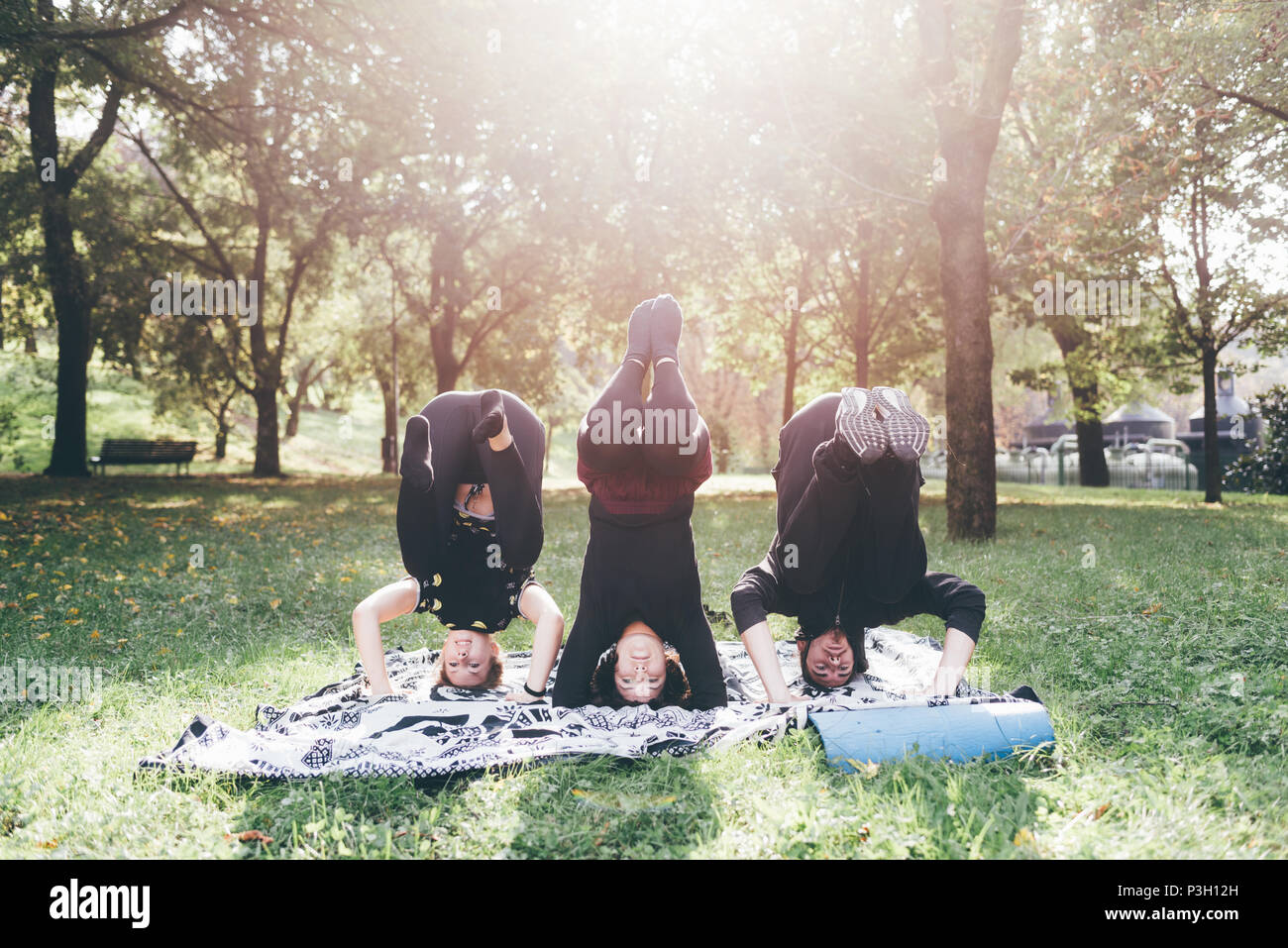 Young man and women stretching outdoor in a city park in sunny day - sportive, training, wellness concept - Stock Image